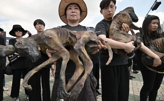 Južnokorejski aktivisti za pravice živali so v rokah nosili mrtve pse med protestom proti trgovini s pasjim mesom pred Državnim zborom v Seulu. Meso kuhanega psa je že dolgo del kuhinje in ostaja poslastica za nekatere v Južni Koreji, saj naj bi se letno zaužilo okoli milijon psov. FOTO: Jung Yeon-je/AFP