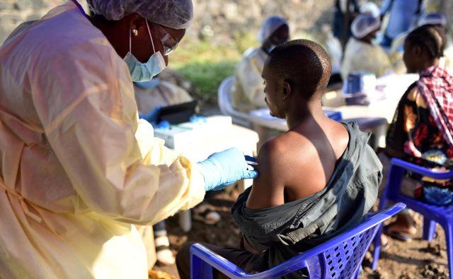 Kongovski zdravstveni delavec daje cepivo ebole moškemu v zdravstvenem centru Himbi v Gomi. FOTO: Olivia Acland/Reuters