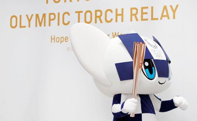 Maskota Miraitova izhaja iz besed Mirai (prihodnost) in Tova (večnost), na fotografiji pozira z olimpijsko baklo. Foto Reuters