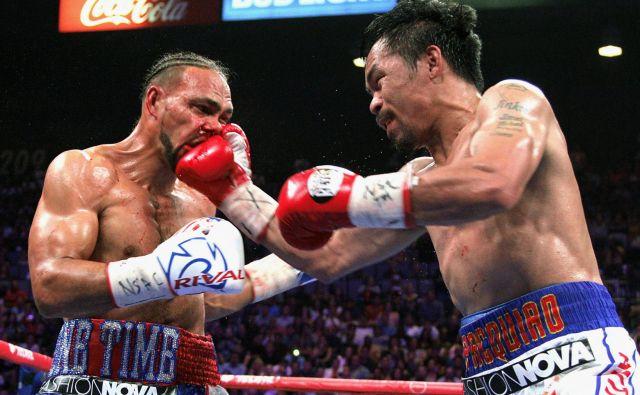 Filipinski boksar Manny Pacquiao je pri 40 letih znova postal svetovni prvak v velterskem razredu. Eden najboljših boksarjev vseh časov, ki je doslej osvojil naslove kar v osmih razredih, je v noči iz sobote na nedeljo v Las Vegasu premagal aktualnega absolutnega prvaka po verziji WBA Američana Keitha Thurmana. FOTO: John Gurzinski/AFP