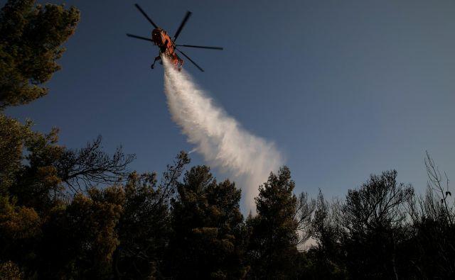 Pri gašenju si pomagajo tudi s helikopterji. FOTO: Alkis Konstantinidis/Reuters