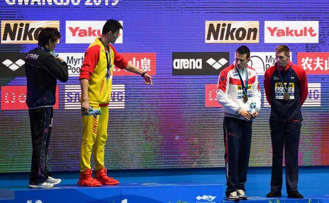 Svetovni prvak na 200 m prosto Sun Yang (drugi z leve), ob katerem je srebrni Japonec Macumoto, je na najvišjo stopničko povabil Rusa Maljutina in Britanca Scotta, ki sta si delila tretje mesto. Slednji ga je zavrnil. FOTO: AFP