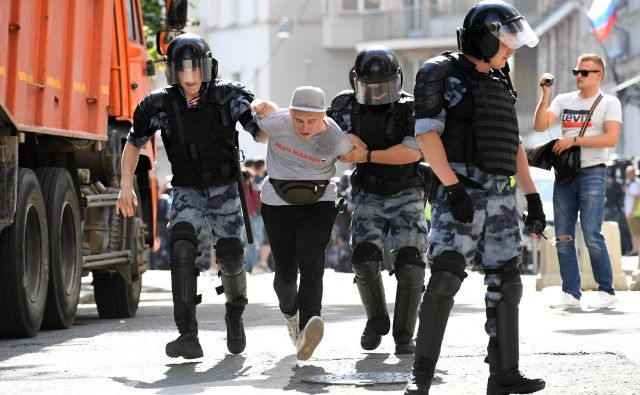 Policija med prijetjem enega od opozicijskih protestnikov. FOTO: Kirill Kudryavtsev/AFP