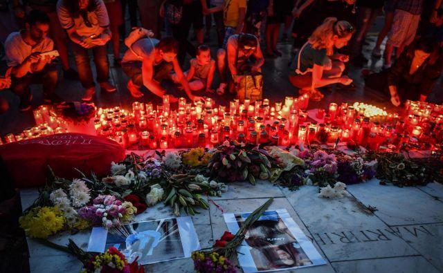 Ljudje prižigajo sveže ob spominskem obeležju pred notranjim ministrstvom. FOTO: Daniel Mihailescu/AFP