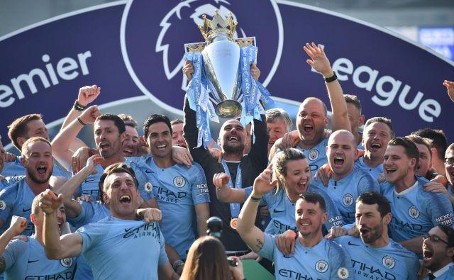Strateg Manchester Cityja Pep Guardiola je 12. maja letos tako dvignil pokal za naslov zmagovalca premier league, obkrožen s svojimi nogometaši in njihovimi družinskimi člani. ManCity je prvi favorit za lovoriko tudi v sezoni, ki jo bodo odprli ta petek v Liverpoolu. FOTO: AFP
