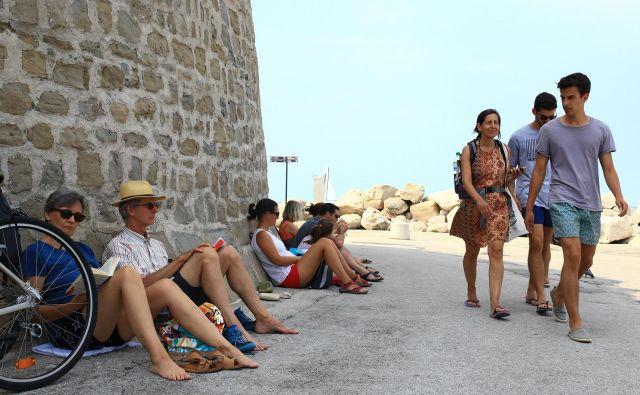 V opoldanski vročini se turisti zatekajo v senco. FOTO: Tomi Lombar