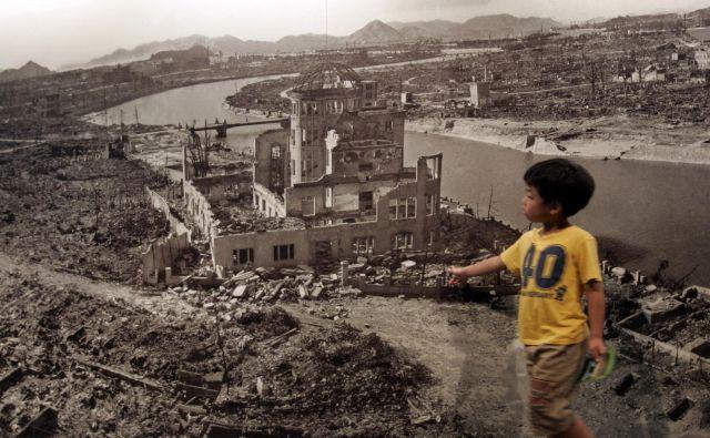 Deček pred fotografijo Hirošime leta 1945, ko jo je opustošila atomska bomba. FOTO: Reuters