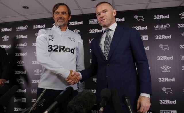 Wayne Rooney (desno) in trener kluba Derby County Phillip Cocu sta si takole segla v roke na novinarski konferenci ob začetku skupne poti. FOTO: AFP