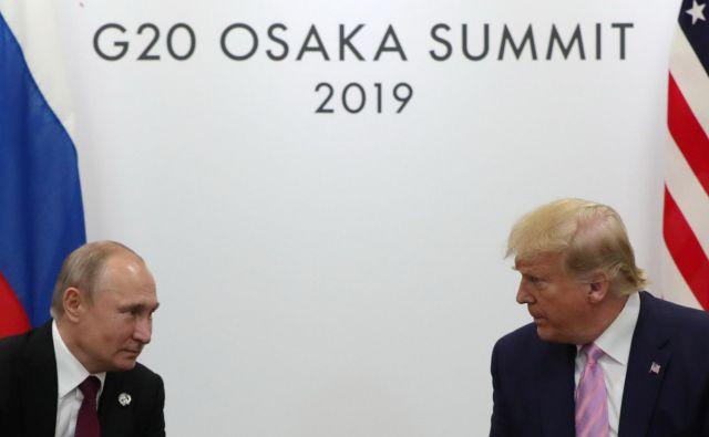 Ruski predsednik Vladimir Putin in ameriški predsednik Donald Trump med njunim srečanjem ob robu vrha skupine države G20 v Osaki.FOTO: AFP