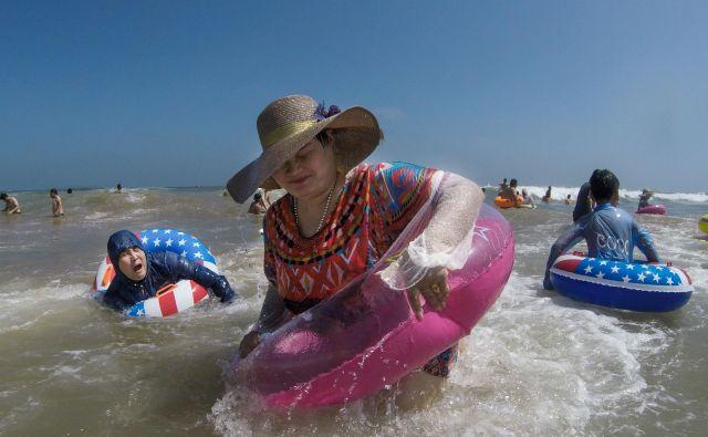 Kitajci se hladijo na plaži v Qingdau na vroč poletni dan. FOTO: Fred Dufour/AFP