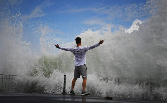 Moški izziva valove, ki butajo v valobran, na otoku Enošima, jugozahodno od Tokia. FOTO: Charly Triballeau/AFP