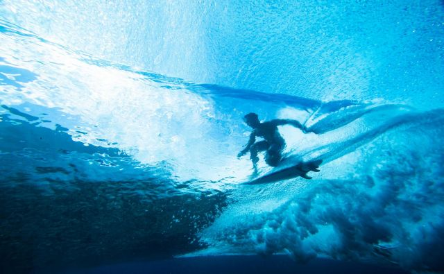 Pogled iz morske gladine na deskarja ki surfa na vodni gladini ob obali polinezijskega otoka Tahiti. FOTO: Brian Bielmann/AFP