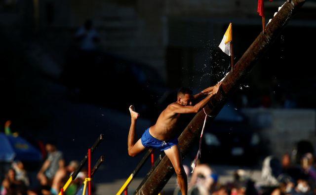 V malteškem mestu St Julian poteka enotedensko praznovanje v čast zaščitniku mesta svetemu Janezu. Eden od najbolj zanimivih dogodkov jetekmovanje, kako na koncu droga, namazanega z mastjo, priti do zastavice. FOTO: Darrin Zammit Lupi/REUTERS