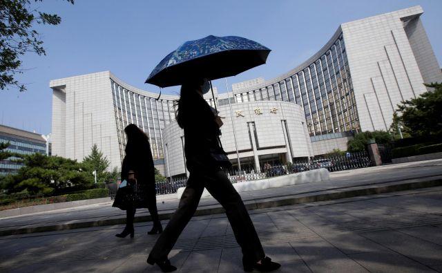 Ugotovili so tudi, da korporacije pretežni delež svojega zaslužka uporabljajo za poplačilo dolga. Na fotografiji v ozadju kitajska banka. Foto: Reuters