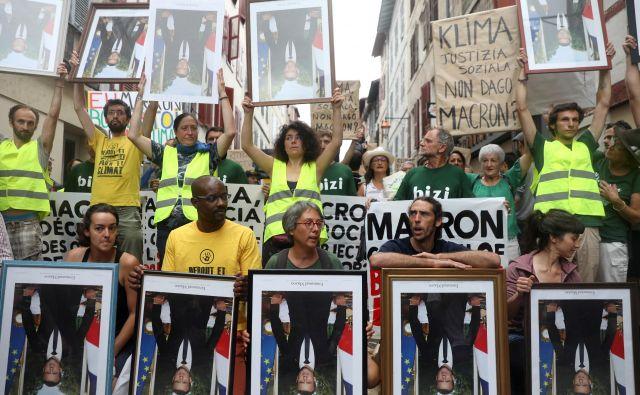 Demonstranti v mestu Bayonne z na glavo obrnjenimi fotografijami francoskega predsednika. Ko so se demonstracije razvnele, je policija razgnala protestnike z vodnimi topovi in solzivcem. FOTO: Reuters