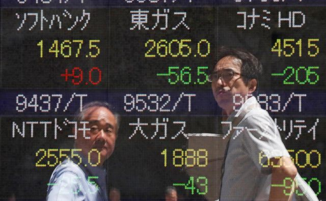 Passersby are reflected on a stock quotation board outside a brokerage in Tokyo, Japan, August 6, 2019. REUTERS/Issei Kato - RC1A93D48210 Foto Issei Kato Reuters