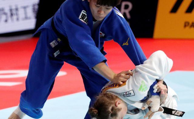 Za Tino Trstenjak (desno) je bil včeraj na svetovnem prvenstvu v Tokiu usoden nedovoljen vzvod na roki japonske zvezdnice Miku Taširo. FOTO: Reuters