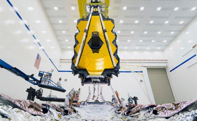 Zadnje napake so odpravljali na sončnem ščitu, ki je že spojen s kapsulo, ki bo celoten instrument ponesla v vesolje. Teleskop so morali zato z dvigalom umestiti v sončni ščit in mehansko in električno povezati obe komponenti. FOTO: Nasa/Chris Gunn