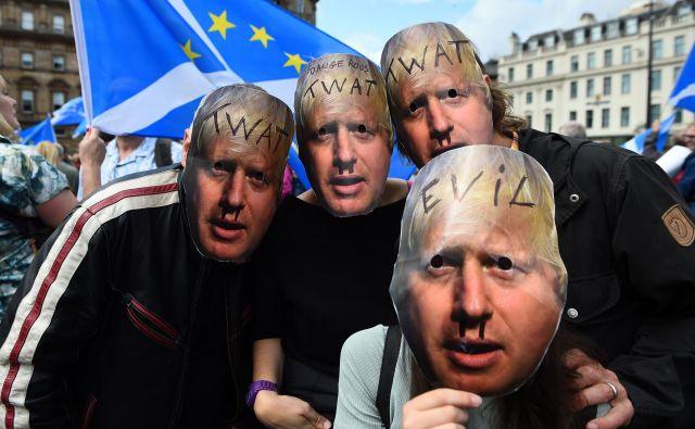 Protestniki z maskami Borisa Johnsona. FOTO: Andy Buchanan/AFP