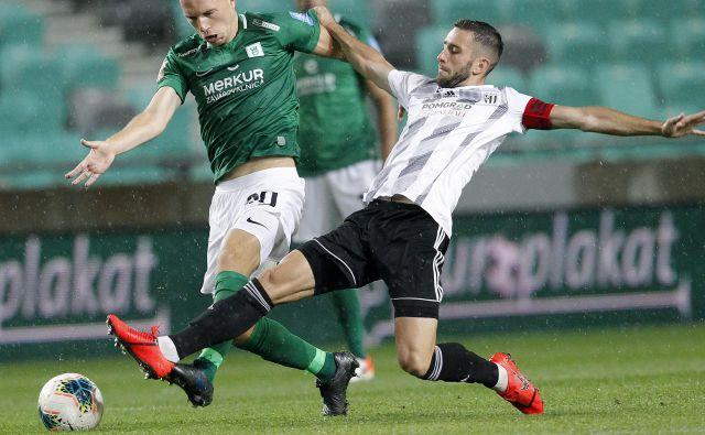Ljubljančani so po hudem boju z desetimi igralci, potem ko je bil v 78. minuti izključen Tomislav Tomić (levo), le prišli do pete prvenstvene zmage. Kapetan Mure Alen Kozar (desno) pa je prvič v sezoni okusil grenkobo poraza. FOTO: Mavric Pivk/Delo