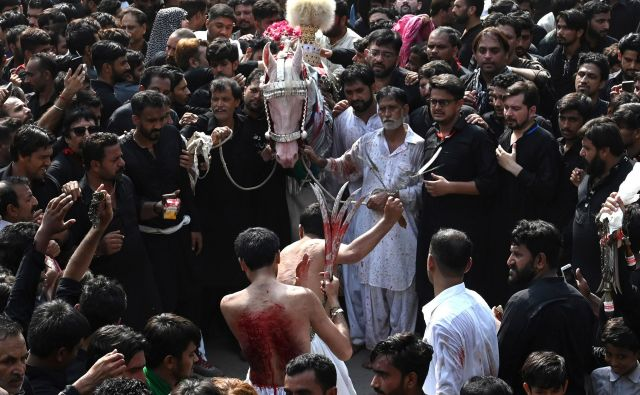 Šiitski muslimani med versko procesijo na deveti dan svetega islamskega meseca muharram v Lahoreju. Islamski mesec muharram zaznamuje sedemstoletno mučeništvo vnuka preroka Mohameda Imama Huseina, ki je bil ubit v bitki pri Karbali v Iraku. FOTO: Arif Ali/AFP