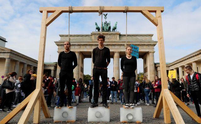 Aktivisti pred Brandenburškimi vrati opozarjajo na segrevanje planeta. FOTO: Fabrizio Bensch/Reuters