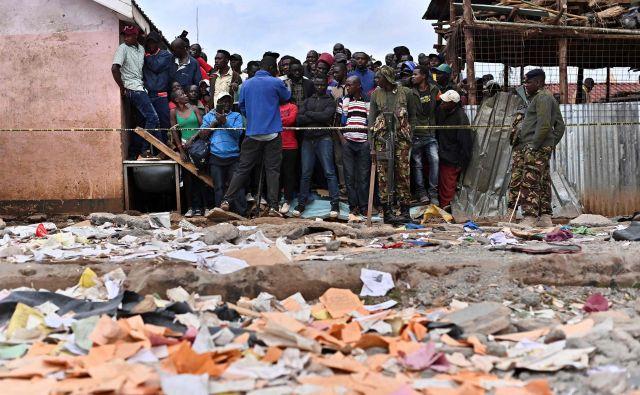 Sorodniki čakajo pred policijskimi trakovi blizu lokacije, kjer se je porušila stavba. FOTO: Tony Karumba/AFP
