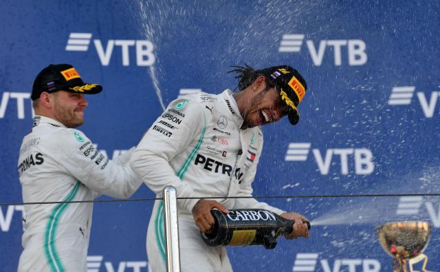 Valtteri Bottas, ki je z drugim mestom zaokrožil dvojno zmago Mercedesa v Sočiju, je s šampanjcem poškropil Lewisa Hamiltona. FOTO: AFP