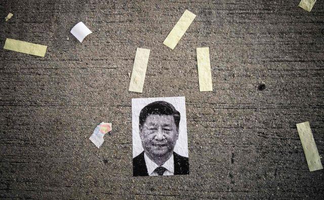 Fotografija kitajskega predsednika, prilepljena na cesto, potem ko so honkogonške ulice preplavili nasilni protesti ob 70. obletnici LR Kitajske. FOTO: AFP