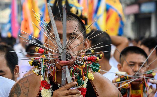 Častitelj kitajskega svetišča s prebodenimi obrazi sodelujejo v povorki med letnim Vegetarijanskim festivalom na tajskem Phuketu. Festival se začne prvi večer devetega lunarnega meseca in traja devet dni , pri čemer se mnogi verniki režejo z meči, z ostrimi predmeti prebijajo obraze in počnejo druga boleča dejanja, da bi se očistili in prevzeli grehe skupnosti. FOTO: Mladen Antonov/AFP