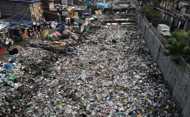 Zgrožujoč pogled na odtočni kanal za odplake, popolnoma prekrit s smetmi in plastiko, v soseski z nizkimi dohodki v New Delhiju. FOTO: Noemi Cassanelli/AFP