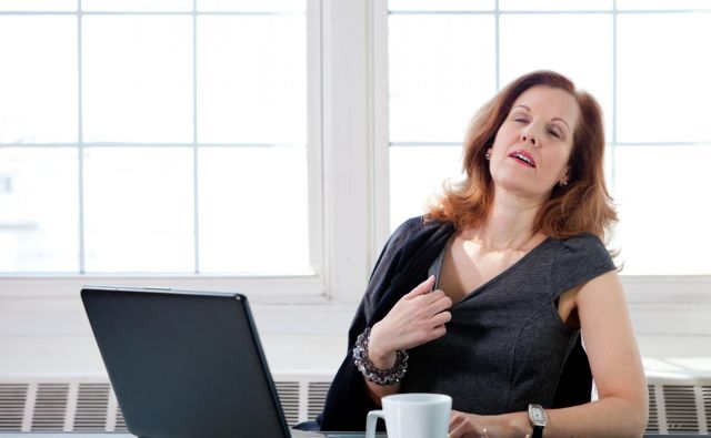 A menopausal woman having a hot flash at her desk in an office. Foto Diane39 Getty Images/istockphoto