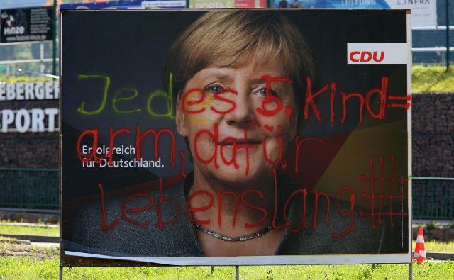 »Vsak peti otrok je reven, zato dosmrtni zapor.« Grafit med volilno kampanjo Angele Merkel. FOTO: Matthias Schumann/Reuters