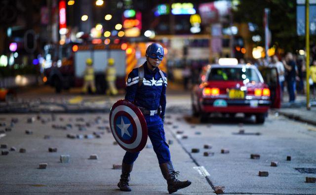 Moški, ki nosi kostum Captain America, hodi po ulici, ko se protestniki zbirajo v bližini policijske postaje v Hongkongu. Hongkong je pretreslo sveže nasilje, ko je več deset tisoč protestnikov ponovno stopilo na ulice, tokrat zaradi prepovedi mask za obraz. FOTO: Mohd Rasfan/AFP