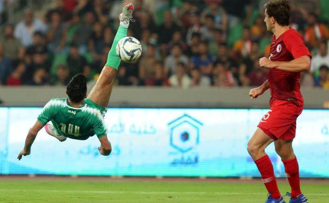 Iračan Amjad Attwan je z atraktivnim poskusom želel zabiti gol. Ni bil uspešen, a je Irak vseeno dosegel prvo kvalifikacijsko zmago pred domačimi navijači v Basri. FOTO: AFP