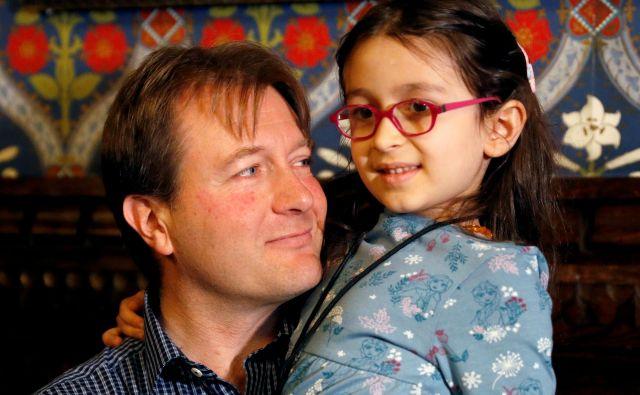 Richard Ratcliffe, mož zaprte britansko-iranske humanitarne delavke Nazanin Zaghari-Ratcliffe, z njuno petletno hčerko Gabriello med tiskovno konferenco v Londonu. Foto REUTERS/Peter Nicholls