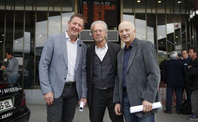 Peter Handke (na sredini) je včeraj preko Brnika pripotoval v rojstno okolje. FOTO: Leon Vidic/Delo