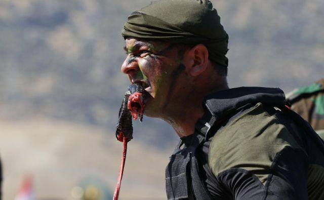 Iraški kurdski Pešmerga častnik je odgriznil kačo, medtem ko je demonstriral spretnosti med podelitvijo diplom v kurdskem mestu Soran, približno 100 kilometrov severovzhodno od glavnega mesta iraške avtonomne kurdske regije Arbil. FOTO: Safin Hamed/AFP