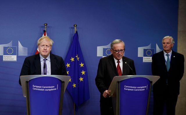 Britanski premier Boris Johnson, predsednik evropske komisije Jean-Claude Juncker in glavni pogajalec za brexit Michel Barnier med novinarsko konferenco v Bruslju. FOTO: Kenzo Tribouillard Afp