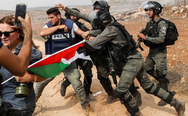 Izraelski mejni policisti napadajo fotoreporterja med demonstracijami proti izraelski gradnji v bližini palestinske vasice Turmus Ayya, severno od Ramallaha na okupiranem Zahodnem bregu. FOTO: Jaafar Ashtiyeh/AFP
