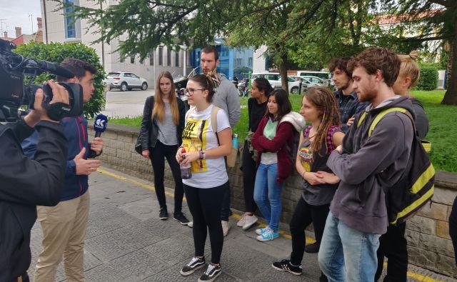 Študentka s plastenko, v kateri je imela črnilo za volilno skrinjico, in skupina študentskih protestnikov daje izjavo za medije.