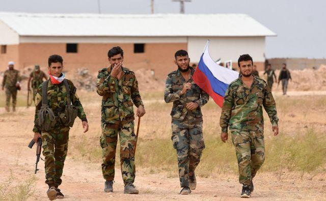 Pripadniki sirskih vladnih sil z rusko zastavo. Foto: AFP