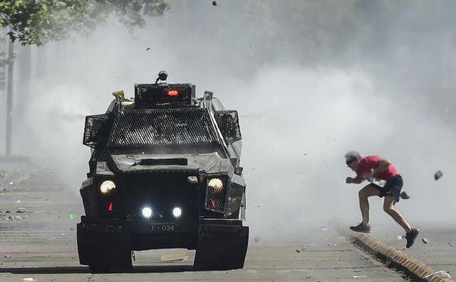 V nemirih v Čilu je doslej umrlo najmanj 13 ljudi, predsednik Pinera pa poskuša stvari umiriti. FOTO: Martin Bernetti/AFP