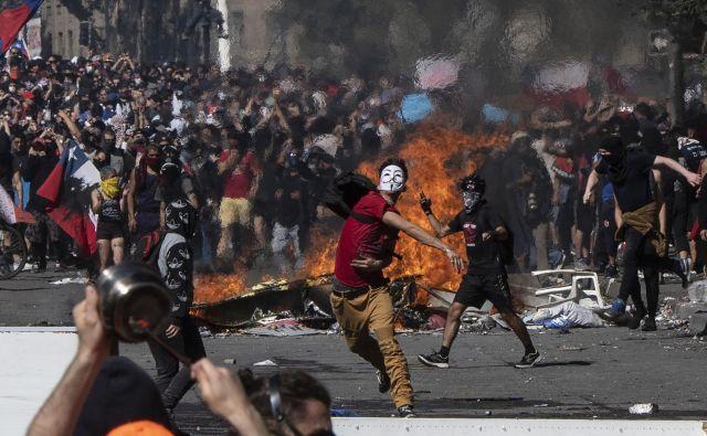 Protivladni protesti, ki se v Čilu nadaljujejo, so doslej zahtevali najmanj 15 žrtev. Predsednik Sebastian Pinera je zato v televizijskem nagovoru opozicijo pozval k pogovorom in predlagal družbeni dogovor za izpolnitev zahtev protestnikov. V govoru v predsedniški palači La Moneda je Pinera opozicijo pozval k sodelovanju z vlado pri iskanju rešitev za socialno krizo v državi. vlada pripravlja načrt obnove. Cilji so med drugim zvišanje pokojnin, znižanje cen zdravil in regulacija cen električne energije. FOTO: Pedro Ugarte/AFP