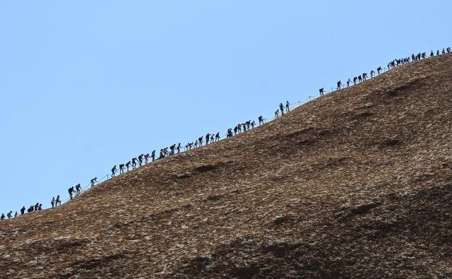 Zadnji dan – v petek – so pod avstralsko ikono prihitele množice turistov, ki so lovile zadnjih pet minut za vzpon. V soboto je prepoved namreč začela veljati. Foto Reuters