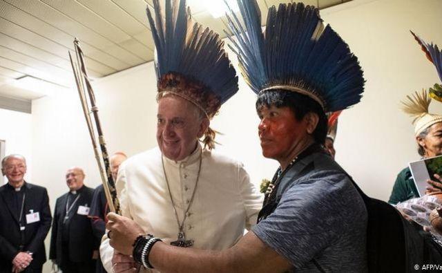Ker je nekatere motila perjanica, ki jo je imel na glavi moški iz Amazonije pri maši ob odprtju sinode, je Frančišek vprašal: »Povejte mi, kakšna je razlika v nošenju perja na glavi ali trikotnih kapic, ki jih nosijo nekateri vatikanski uslužbenci.« Sam je ne vidi, zato si je nadel perjanico. FOTO: AFP