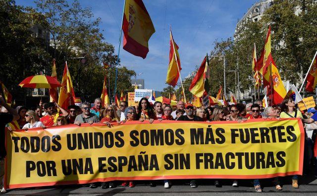 Ljudje ob transparentu z napisom »Skupaj smo močnejši, za Španijo brez zlomov«. FOTO: Josep Lago/AFP