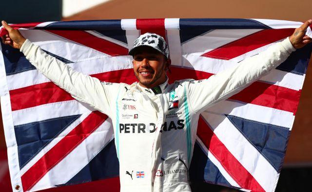 Lewis Hamilton se je z britansko zastavo veselil šestega naslova svetovnega prvaka. FOTO: AFP