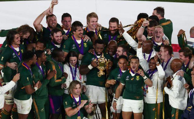 Prvi temnopolti kapetan reprezentance v zgodovini južnoafriškega ragbija Siya Kolisi s pokalom Webba Ellisa po zmagi nad Anglijo v finalu svetovnega prvenstva na Japonskem. Foto Afp
