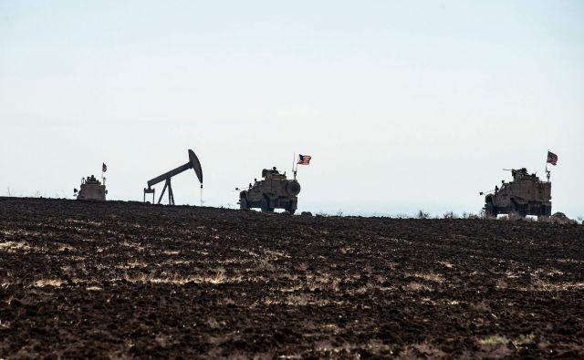 Konvoj ameriških oklepnih vozil nadzira naftno črpališče v provinci Hasaka na severovzhodu Sirije. FOTO: AFP